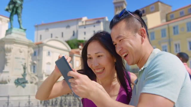 Young Asian couple checking the photos they just took with the tablet as they stand in the town square