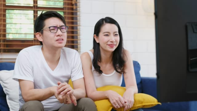 young asian couple cheering sport on television show with excitement emotion at sofa in home living room, people and entertainment - television game show stock videos & royalty-free footage