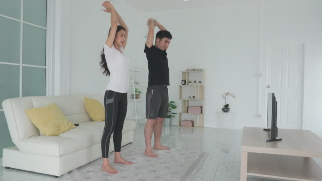 young asian couple doing high-intensity interval training together and looking tv at home, man and woman working out together standing in living room, fit pair performing fitness exercise with partner. - tall high stock videos & royalty-free footage