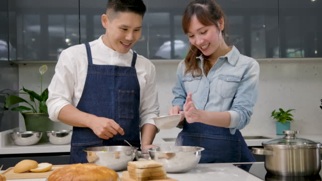 young asian couple have fun dancing and singing while set the table for breakfast in the kitchen at home. - romantic meal stock videos & royalty-free footage