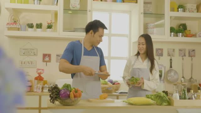 vídeos de stock e filmes b-roll de young asian couple in the kitchen - domestic kitchen