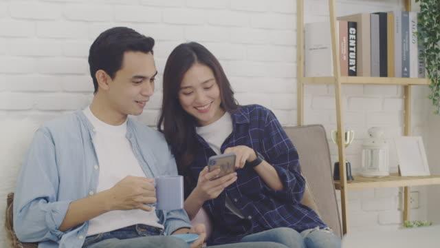 若いアジアのカップルの恋人は、自宅の背景に部屋でオンラインショッピングと一緒にスマートフォンを使用しています。 - living room点の映像素材/bロール