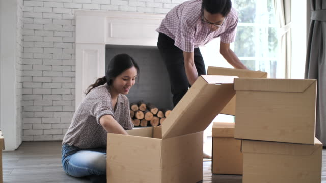 young asian couple moving box into a new home, slow motion - oriental culture stock videos & royalty-free footage