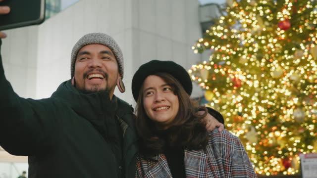 夜にクリスマスフェスティバルを訪れる観光客の若いアジアのカップル。日本 - デート点の映像素材/bロール