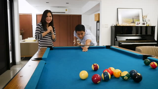 vídeos de stock e filmes b-roll de young asian couple playing billiard in the living room at home - mesa de bilhar