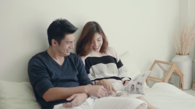 若いアジアのカップルの寝室で読書 - 雑誌点の映像素材/bロール