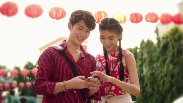vidéos et rushes de jeune couple asiatique qui autoportrait avec le smartphone dans une ville rue - culture chinoise