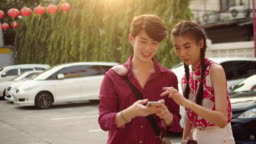 Young asian couple taking self-portrait with smartphone in a city street