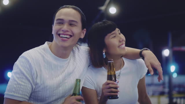 young asian couple toasting with beer at rooftop party - beer bottle stock videos & royalty-free footage