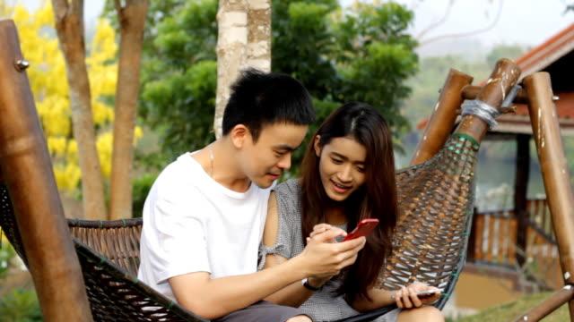 """vídeos de stock, filmes e b-roll de jovem casal asiático com smartphone """" - rede de dormir"""