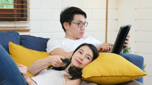 young asian couple watching television with happiness at sofa in home living room background, people and home entertainment - mid adult couple stock videos & royalty-free footage