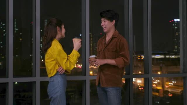 若いアジアのクリエイティブオフィスは、夜にオフィスで話しながらコーヒーカップを立って、遅くまで働いています - casual clothing点の映像素材/bロール