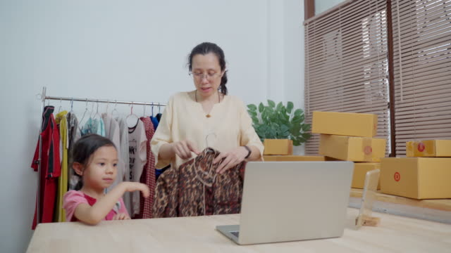young asian daughter help her mother selling clothes online using laptop at apartment - selling stock videos & royalty-free footage