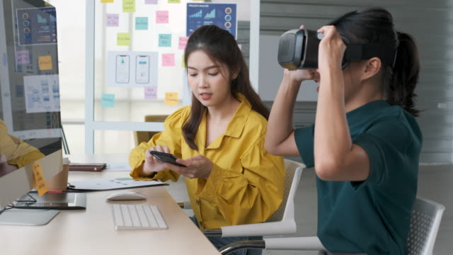 young asian designer team wear vr glasses (virtual reality) testing mobile app ux,ui from develop software with desktop computer at modern creative office.panning - mobile app stock videos & royalty-free footage