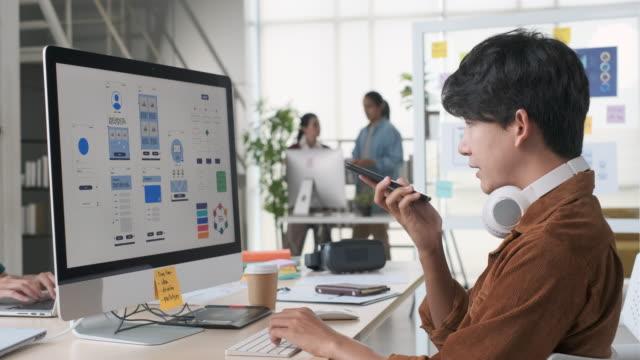 若いアジアの開発者は、創造的なteam.ux uiデザインエージェンシーと現代のオフィスでコンピュータで作業する際に、モバイルアプリ注文スマートオフィスシステムでai(人工知能)音声認識を� - プロトタイプ点の映像素材/bロール