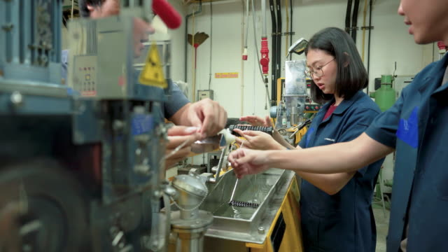 young asian engineer working on a polymer production line to produce polymer extrude with man coworker by using twin-screw extruder. woman engineering, scientist student wearing blue clothes doing polymer experiments with friends. concept of woman in stem - uniform stock videos & royalty-free footage