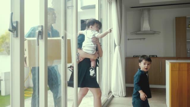 新しい家に引っ越すアジアの若い家族 - 両親点の映像素材/bロール