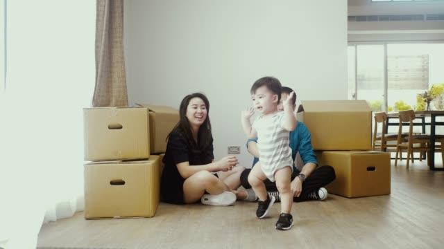 新しい家に引っ越しながら子供と遊ぶ若いアジアの家族 - 段ボール箱点の映像素材/bロール