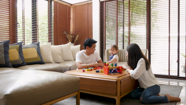 young asian family spending time together in the living room at home - young family stock videos & royalty-free footage