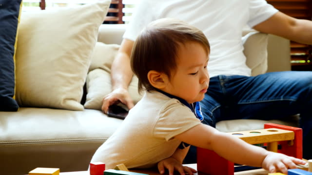 vídeos de stock, filmes e b-roll de jovem família asiática a passar tempo juntos na sala de estar em casa - bloco de construção