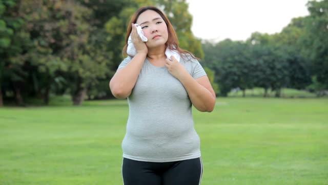 Ung asiatisk kvinna trött fett i parken