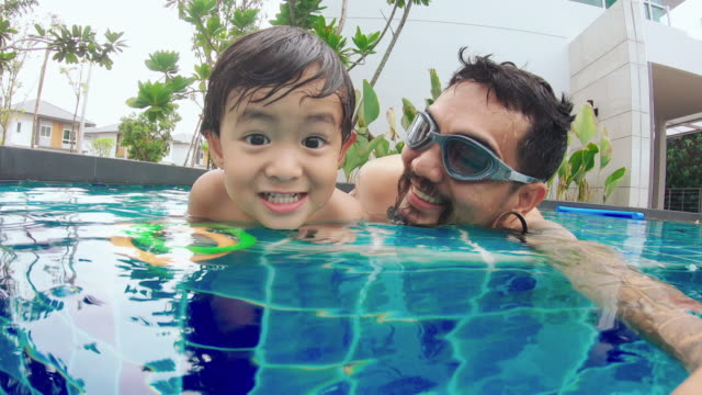 young asian father and baby boy swim in pool - baby boys stock videos & royalty-free footage
