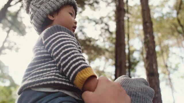 junge asiatische vater sein baby in holz im winter zu tragen. - auf den schultern stock-videos und b-roll-filmmaterial
