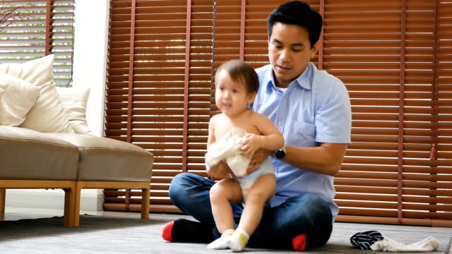 young asian father changing clothes for  little baby boy at home - genderblend video stock e b–roll