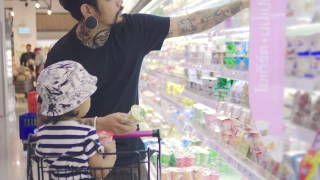 young asian father chooses dairy produce in the store - label stock videos & royalty-free footage