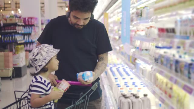 Young asian father chooses dairy produce in the store
