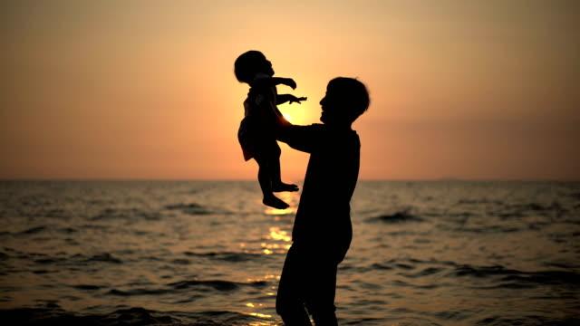 young asian vater holding baby boy bis zum sonnenuntergang am strand. - männliches baby stock-videos und b-roll-filmmaterial