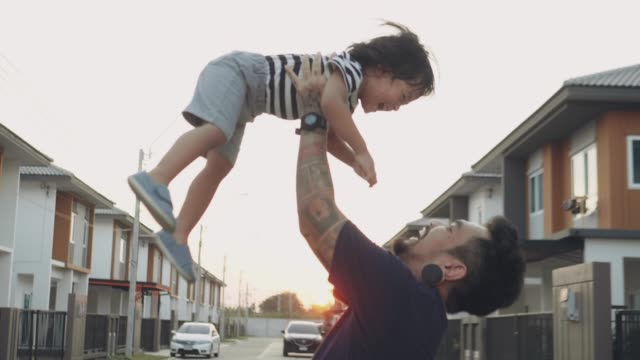 young asian father lifting his son up in air. - picking up stock videos & royalty-free footage