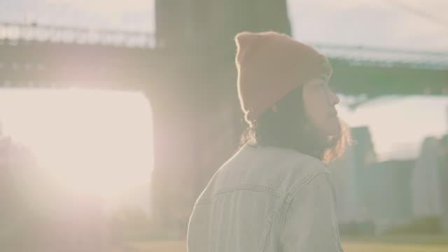 Joven mujer asiática en el río tomando fotos del puente con cámara digital.