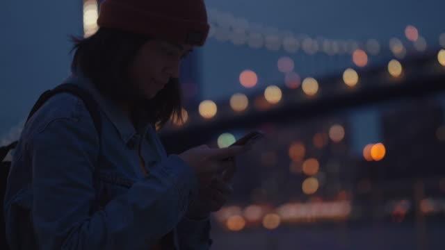 スマート フォンで橋の写真を撮って川で若いアジア女性 - 整える点の映像素材/bロール