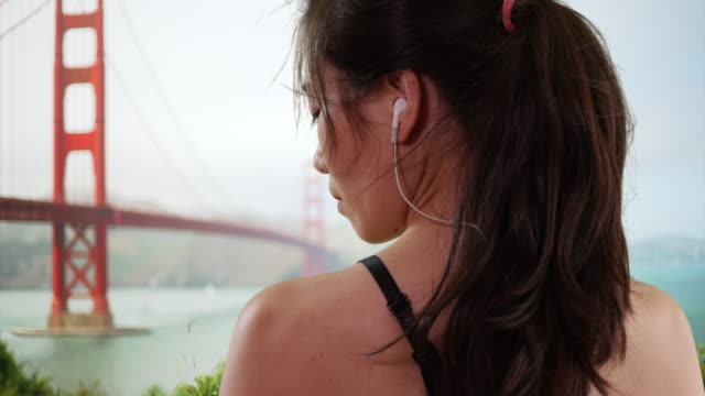 stockvideo's en b-roll-footage met young asian female athlete resting and listening with earbuds in bay area - in ear koptelefoon