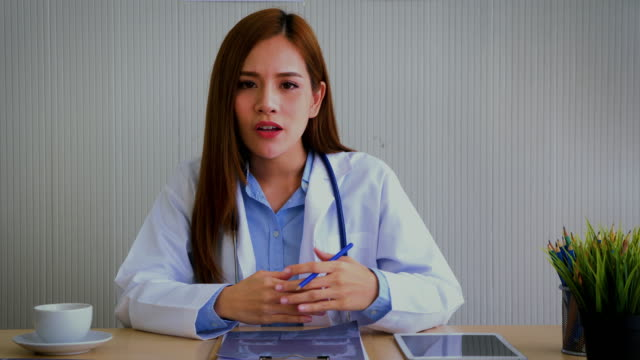 young asian female doctor talking and looking to camera in video conference - talking stock videos & royalty-free footage