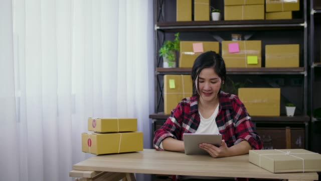 vídeos de stock e filmes b-roll de young asian female freelancer using her digital tablet and working at home, small business female owner or start up small business entrepreneur working online marketing packaging box delivery - e commerce