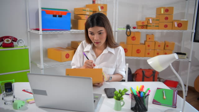 vídeos de stock e filmes b-roll de young asian female freelancer using her digital tablet and working at home, small business female owner or start up small business entrepreneur working online marketing packaging box delivery - business casual