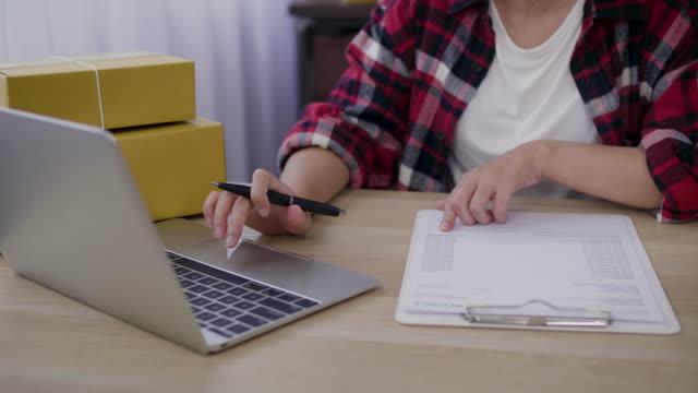 junge asiatische frauen freiberufler mit ihrem laptop und arbeiten von zuhause, weibliche inhaber eines kleinen unternehmens oder start-up small business unternehmer arbeiten online-marketing-verpackung box lieferung - ausverkauf stock-videos und b-roll-filmmaterial