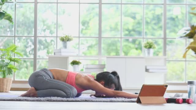 若いアジアの女性は自宅で運動をしている、アスレチックの女性はヨガを練習し、デジタルタブレット、ウェル、4k解像度でフィットネスチュートリアルレッスンを見ています - 女性選手点の映像素材/bロール