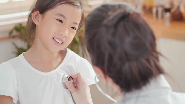 young asian female nurse doctor examining a little girl by stethoscope at home. medical, caretaking, care, children, family, volunteer, education, nursing home, caregivers at home, medicine and health care, medical consultation, home healthcare - trust stock videos & royalty-free footage