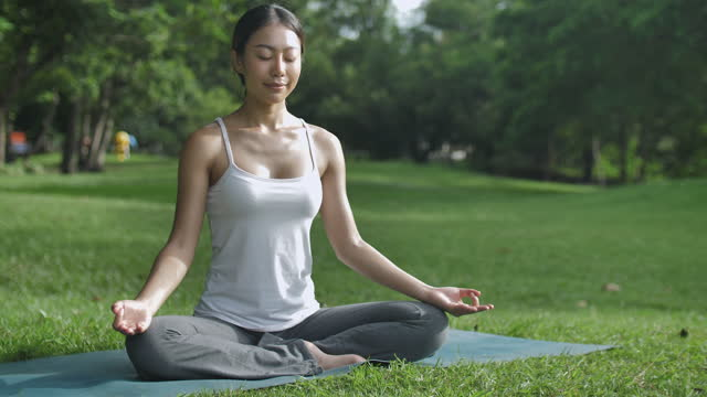 young asian female practicing yoga in the public park - lotus position stock videos & royalty-free footage