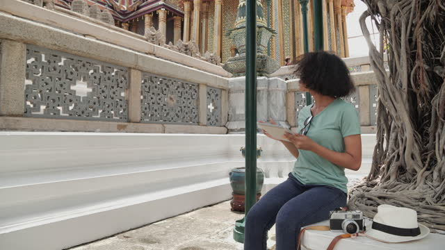 young asian female using a smartphone while standing on the street beside wat phra kaew in thailand and having fun in vacation time. - 社会史点の映像素材/bロール