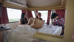 Young asian female wake up having pillow fight with their friends on the bed in camper van