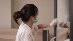 Young asian female wear protective gloves cleaning her mirror by spraying and wiping, disinfects home furniture, hygiene health care, sanitize household day light, coronavirus covid19, model wear mask