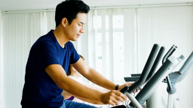 Young Asian fitness man using cycling exercise bikes at the gym,  Cardio training concept