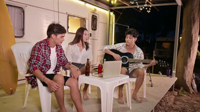 vídeos de stock, filmes e b-roll de jovens amigos asiáticos curtindo ponto de encontro e tocando guitarra na van campista nas férias - comboio