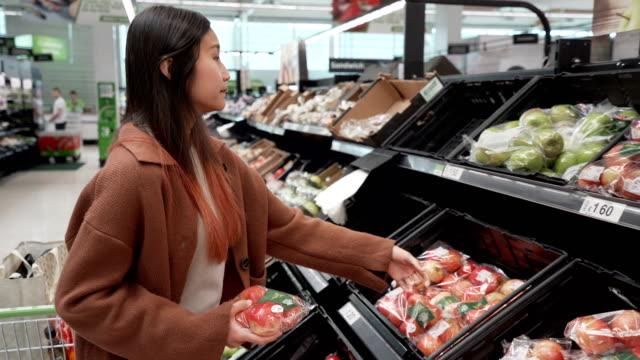 若いアジアの女の子は野菜を選ぶ - ほっそりした点の映像素材/bロール