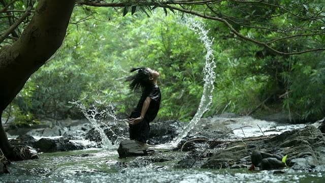 young asian girl playing splashing water in the river. shooting with a slow-motion shot. - falling water stock videos & royalty-free footage