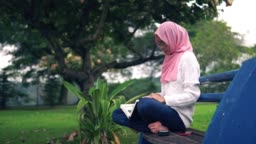 Young asian girl reading book outdoor